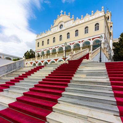 Treppe mit rotem Teppich zur orthodoxen Wallfahrtskirche Panagia Evangelistria in Tinos-Stadt auf der griechischen Kykladeninsel