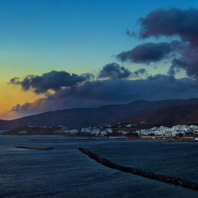 Panorama von Tinos Stadt zum Sonnenuntergang hinter der griechischen Kykladeninsel Syros